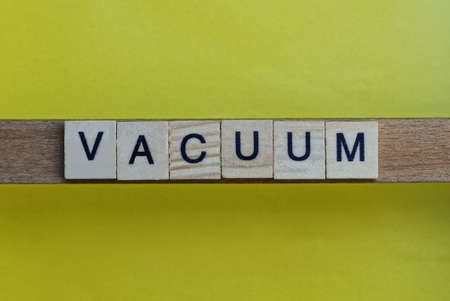 gray word vacuum in small square wooden letters with black font on a yellow background