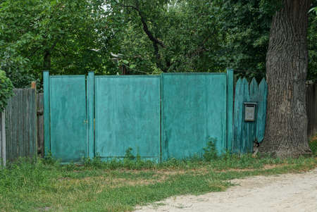 iron green gate and rural wooden fence on the street