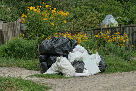 a pile of rubbish from white and black full plastic bags on gray ground among green grass and yellow flowers outside