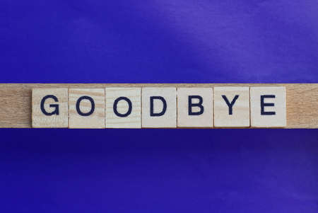 text on gray word goodbay in small wooden letters with black font on a lilac background Stockfoto