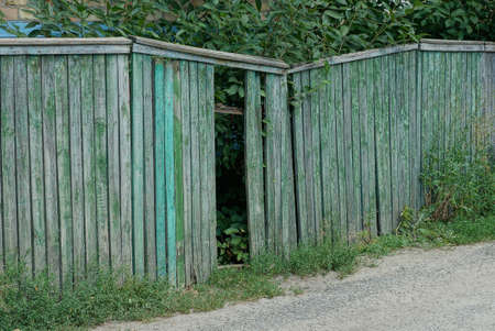 part of a green wooden old fence with broken boards on a rural street Stockfoto