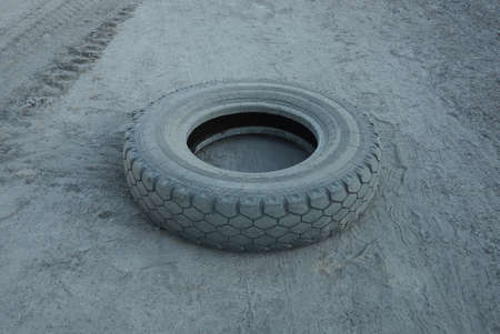 one old big truck tire lies on the gray sand of the road