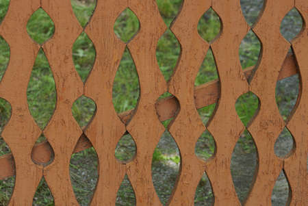brown texture of wooden boards in a fence wall with a carved pattern