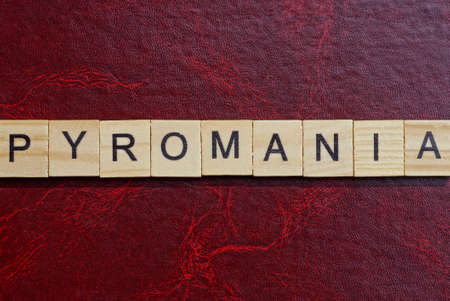 text the word pyromania from gray wooden small letters with black font on an red table