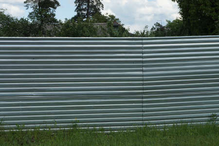 part of a gray metal fence wall in green grass on a rural street