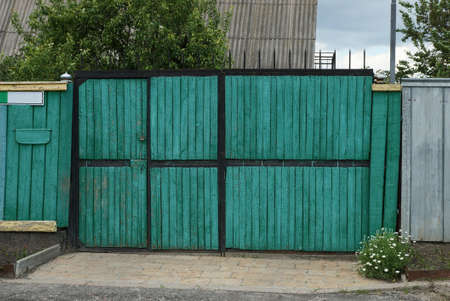 one closed green wooden gate on a rural street