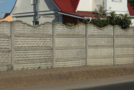 a fragment of a gray wall of a concrete private fence on a rural street in the ground by the road