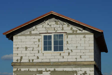 white brick attic of a private house with one window against a blue sky Stockfoto
