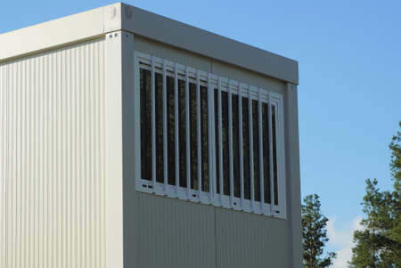 one white window with iron bars on a gray metal container against a blue sky