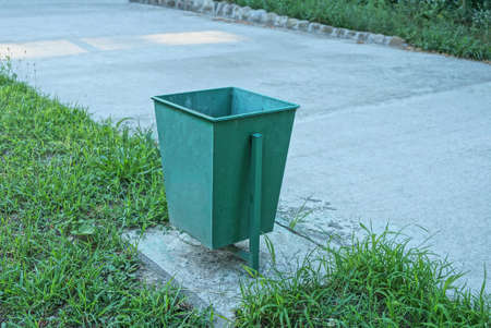 one empty metal green urn stands by a gray concrete road in the grass outside in a park Stockfoto