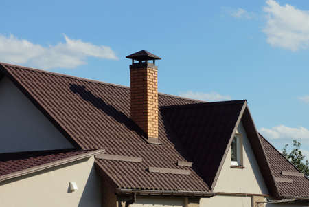 brown tiled roof of a gray private house with a window and one brick chimney against a blue sky Stockfoto