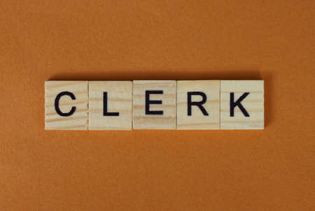 gray word clerk made of wooden square letters on brown background Stockfoto