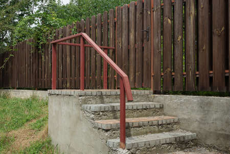 gray concrete steps ir red iron handrails outside by a wooden brown fence wall Standard-Bild