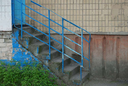 old staircase with gray concrete steps and blue iron railing against a brown wall outside