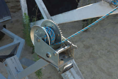 part of a gray iron winch with a blue rope on the street