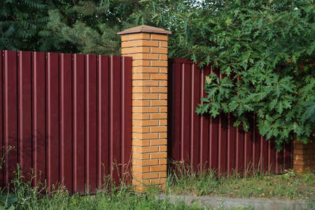 red wall of a fence made of metal and bricks overgrown with green vegetation and grass on the street