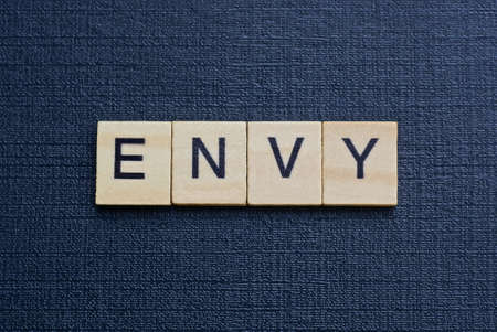 gray word envy from small wooden letters on a black table Standard-Bild