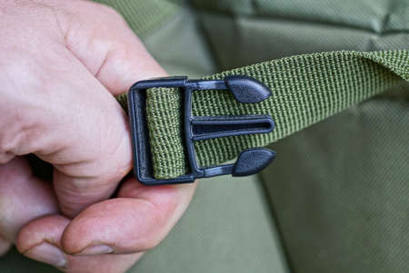 hand holds open black plastic carabiner on the green harness of the backpack