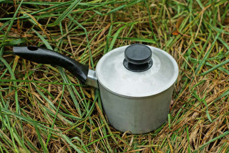one gray closed cast iron pan with a black handle stands in green grass in nature
