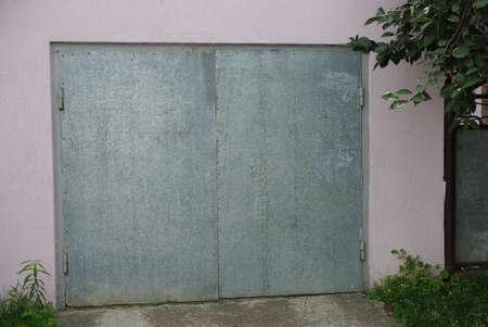 gray iron gate on pink concrete wall of garage on street 版權商用圖片
