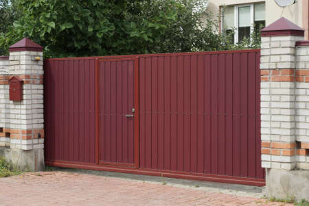 one large red closed metal gate and part of a fence made of white bricks outside