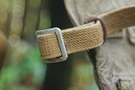 green fabric harness with gray metal carbine on an old army backpack Фото со стока