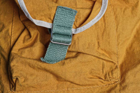 metal carabiner rings with gray straps on the brown fabric of the backpack