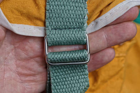 hand holds a green harness with metal carabiners on the brown fabric of the backpack