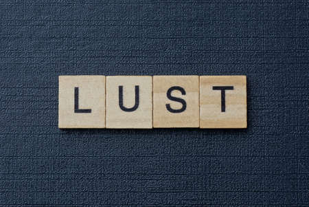gray word from small wooden letters on a black table