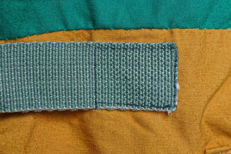 one long green harness patch on the brown fabric of the backpack