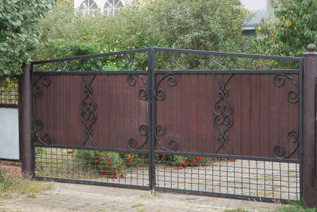 one closed brown iron gate with a black wrought iron pattern on a rural street