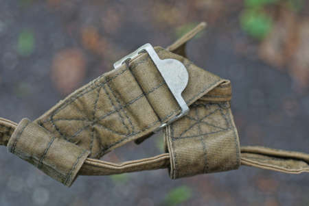 green harness made from the fabric of an old army backpack with a gray metal carabiner
