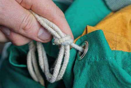 fingers tie a white rope knot on a colored fabric backpack