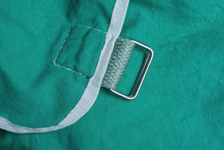 one metal carabine rings with black straps on the green fabric of the backpack