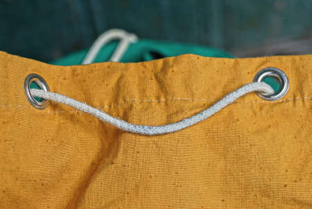 white rope lace in a two gray metal ring on a brown backpack fabric
