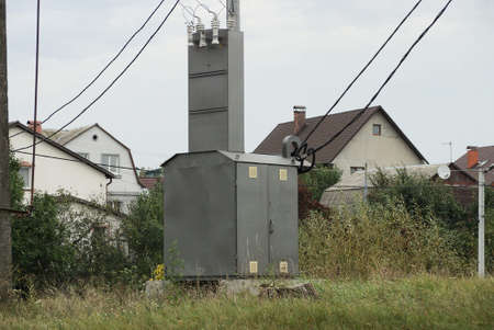 large gray metal transformer box with electric wires outside in green grass against the background of the sky 版權商用圖片