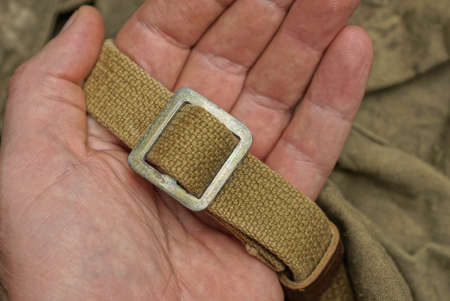 hand hold a gray metal carbine on an old green harness made of fabric on a backpack Фото со стока