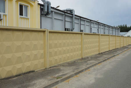 a long yellow concrete fence by an asphalt road in front of an industrial wall of a factory 免版税图像