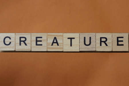 gray word creature made of wooden square letters on brown background
