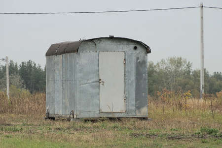 old gray metal trailer stands in the grass on the field
