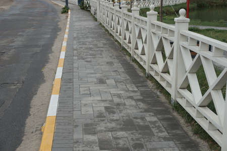 a long alley of gray paving slabs by an asphalt road along a white wooden fence on the street