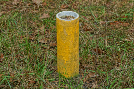 one post limiter made of yellow concrete pipe stands in the green grass outside Stockfoto