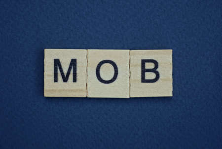 gray word mob from small wooden letters on a black table 版權商用圖片