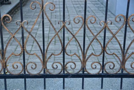 metal texture from a brown forged pattern on black bars of a fence on the street against a gray sidewalk