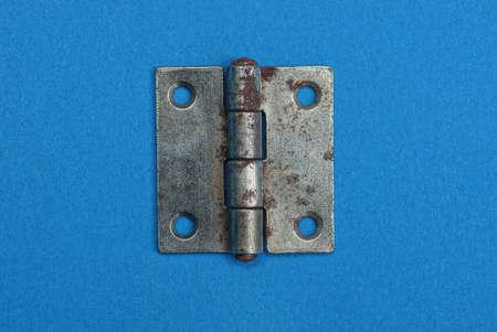 one gray metal door hinge in rust lies on a blue table Reklamní fotografie