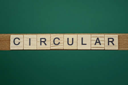 gray word circular made of wooden square letters on green background