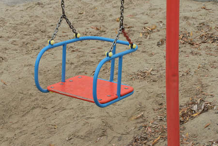 one empty color swing seat hanging on gray iron chains outdoors against brown ground background