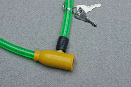 part on a bicycle lock with a yellow metal core and a green plastic cable and two keys lies on a gray table Imagens