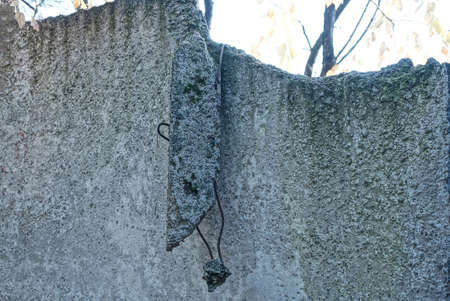 part of a broken gray concrete wall of a fence with a piece of reinforcement on the street