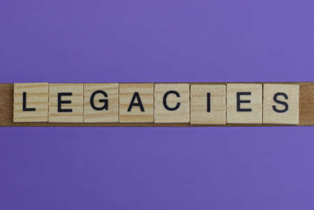 gray word legacies in small square wooden letters with black font on a lilac background